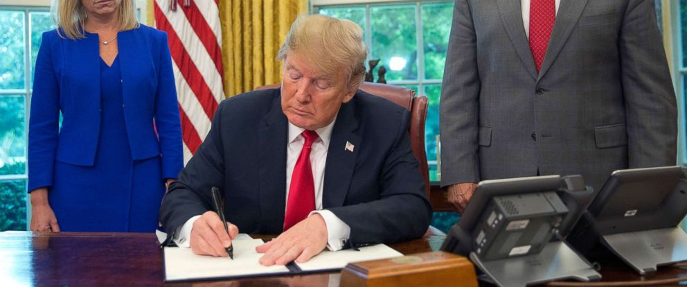 PHOTO: President Donald Trump signs an executive order to keep families together at the border during an event in the Oval Office of the White House on June 20, 2018.