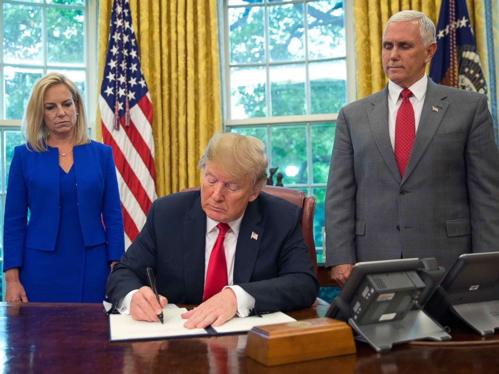 PHOTO: President Donald Trump signs an executive order to keep families together at the border during an event in the Oval Office of the White House in Washington, June 20, 2018.