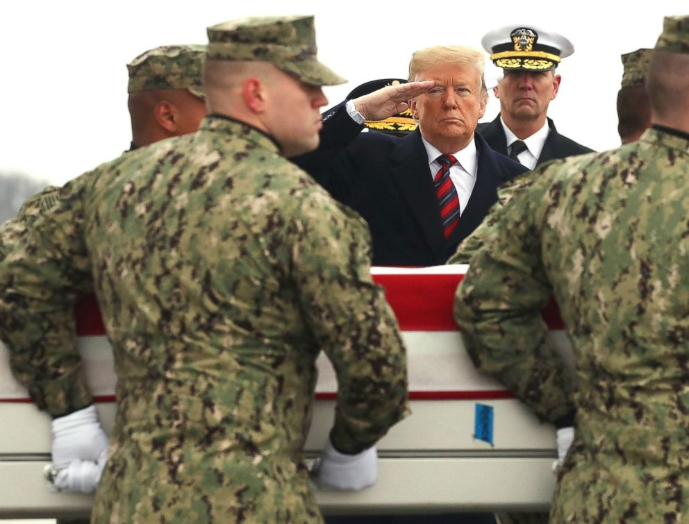 PHOTO: President Donald Trump salutes as a military carry team moves the transfer case containing the remains of Scott A. Wirtz during a dignified transfer at Dover Air Force Base, Jan. 19, 2019, in Dover, Del.