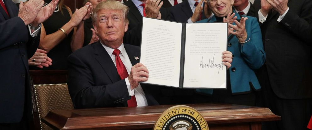 PHOTO: President Donald Trump shows an executive order after he signed it in the Roosevelt Room of the White House, Oct. 12, 2017, in Washington.