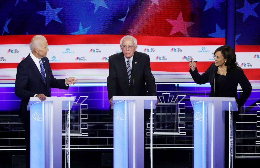 PHOTO: Former Vice President Joe Biden and Sen. Kamala Harris and speak as Sen. Bernie Sanders looks on during the first Democratic presidential debate in Miami, June 27, 2019.