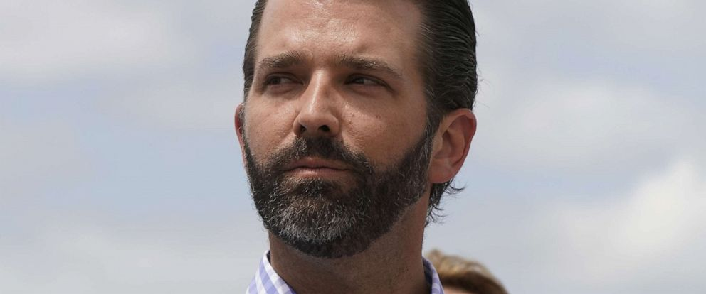 PHOTO: Donald Trump Jr. listens to his father, President Donald Trump, speak during a visit to Lake Okechobee and the Herbert Hoover Dike in Canal Point, Fla., March 29, 2019.