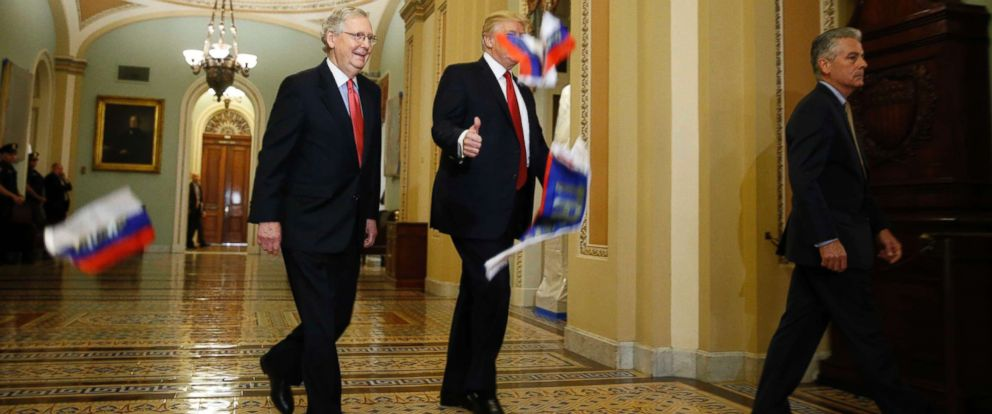 PHOTO: President Donald Trump gestures to reporters as Russian flags thrown from a protester fall in front of the president and Senate Majority Leader Mitch McConnell as they arrive for a Republican luncheon on Capitol Hill in Washington, Oct. 24, 2017.