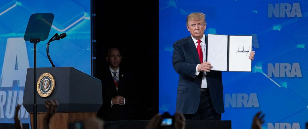 PHOTO: President Donald Trump shows a signed order rejecting the 2013 Arms Trade Treaty as he speaks at the National Rifle Associations Annual Meeting at Lucas Oil Stadium in Indianapolis, April 26, 2019.