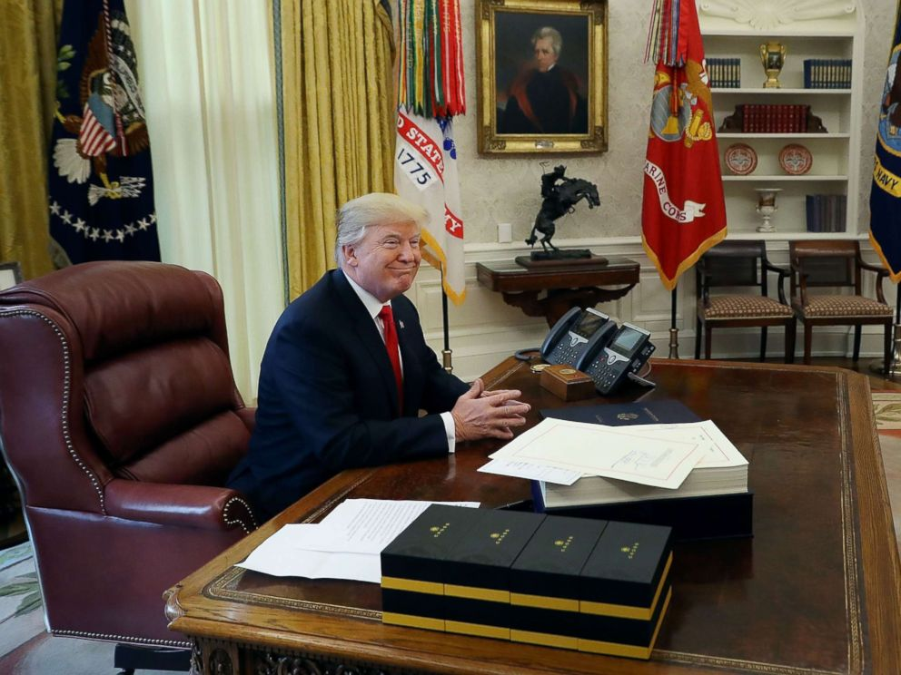 PHOTO: President Donald Trump talks with journalists before signing tax reform legislation into law in the Oval Office Dec. 22, 2017 in Washington.