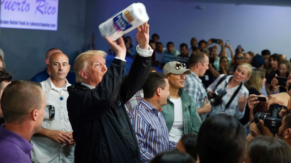 President Donald Trump tosses paper towels into a crowd as he hands out supplies at Calvary Chapel, Oct. 3, 2017, in Guaynabo, Puerto Rico.