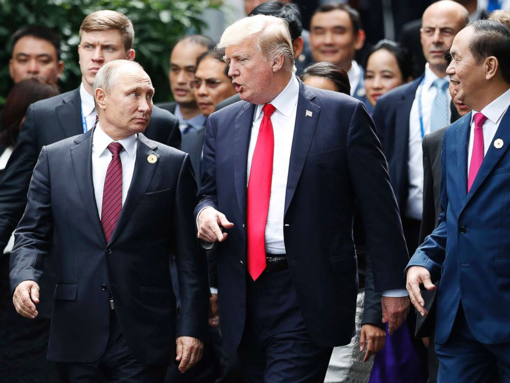 Russias President Vladimir Putin and President Donald Trump talk as Vietnams President Tran Dai Quan right looks on during the family