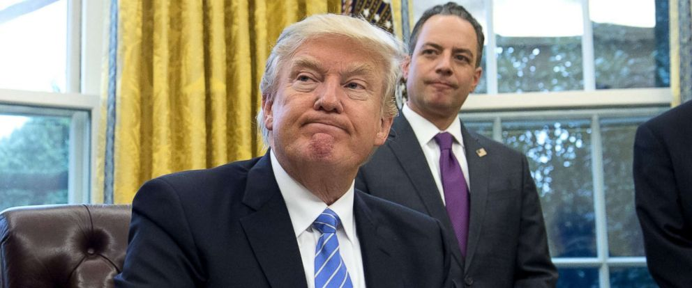 PHOTO: President Donald Trump signs an executive order as Chief of Staff Reince Priebus looks on in the Oval Office of the White House in Washington, D.C., Jan. 23, 2017.