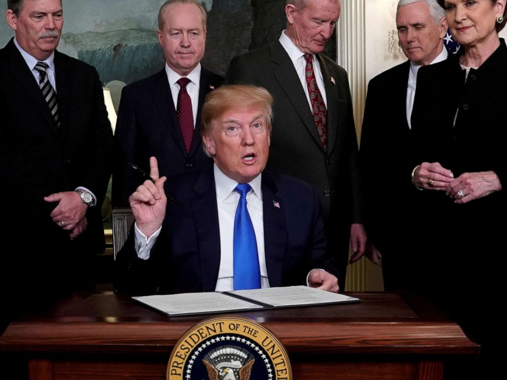 PHOTO: President Donald Trump, surrounded by business leaders and administration officials, prepares to sign a memorandum on intellectual property tariffs on high-tech goods from China, at the White House in Washington, March 22, 2018.