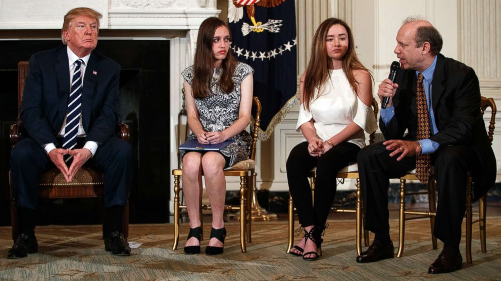 From left, President Donald Trump, Marjory Stoneman Douglas High School students Carson Abt and Ariana Klein, listen as Carson's father Frederick Abt, speaks during a listening session with high school students, teachers, and others in the State Dining Room of the White House in Washington, D.C., Feb. 21, 2018.