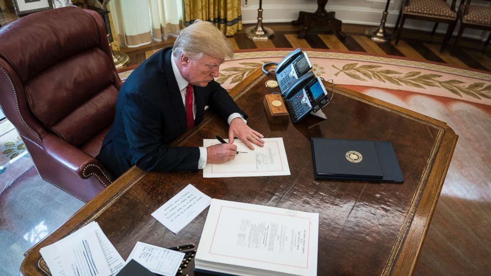 President Donald Trump signs the Tax Cut and Reform Bill, a $1.5 trillion tax overhaul package, into law in the Oval Office at the White House in Washington, D.C., Dec. 22, 2017.