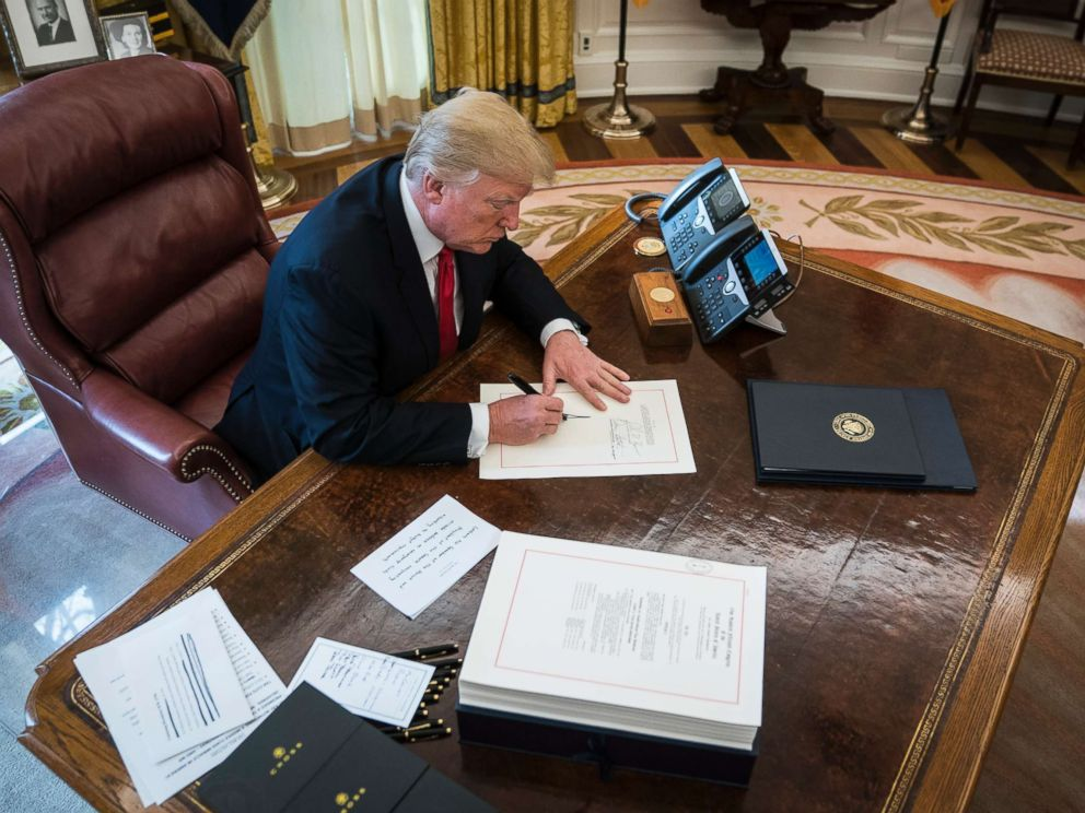 PHOTO: President Donald Trump signs the Tax Cut and Reform Bill, a $1.5 trillion tax overhaul package, into law in the Oval Office at the White House in Washington, D.C., Dec. 22, 2017.