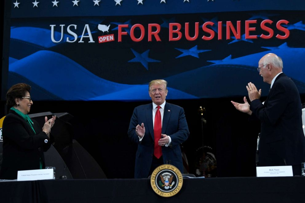 PHOTO: President Donald Trump, center, arrives to speak during a roundtable discussion at Nuss Truck and Equipment in Burnsville, Minn., Monday, April 15, 2019, during an event to tout the 2017 tax law.