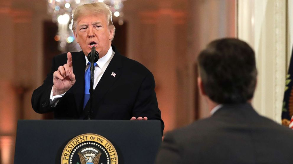 President Donald Trump speaks as CNN's Jim Acosta, standing at right, listens, during a news conference in the East Room of the White House, Nov. 7, 2018, in Washington.