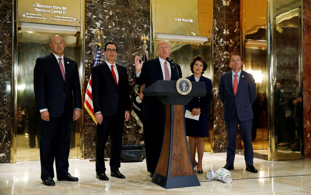 PHOTO: President Donald Trump is flanked by officials as he speaks about the violence in Charlottesville while talking to the media in the lobby of Trump Tower in New York, Aug. 15, 2017.