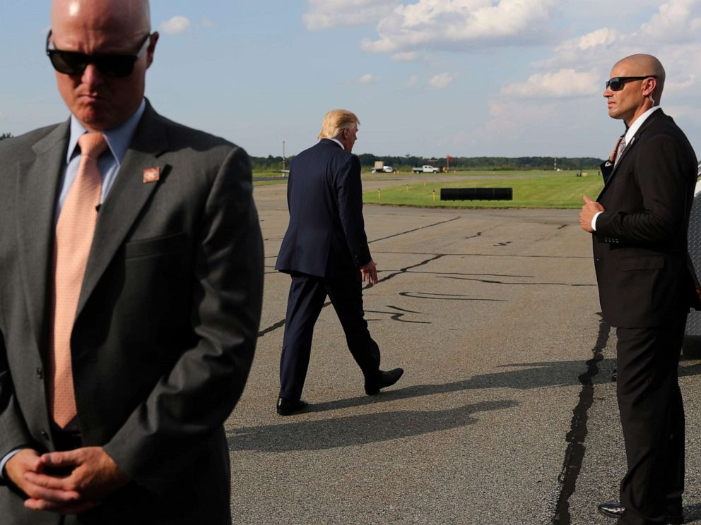 PHOTO: U.S. Secret Service agents guard President Donald Trump as he boards Air Force One to return to Washington from Morristown Municipal Airport in Morristown, New Jersey, Aug. 18, 2019.