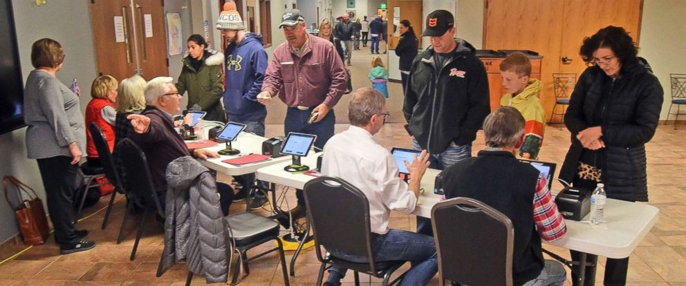 PHOTO: Election workers check identification of each person before receiving a ballot at the northwest Bismarck, N.D., polling place in Century Baptist Church on Tuesday, Nov. 6, 2018.