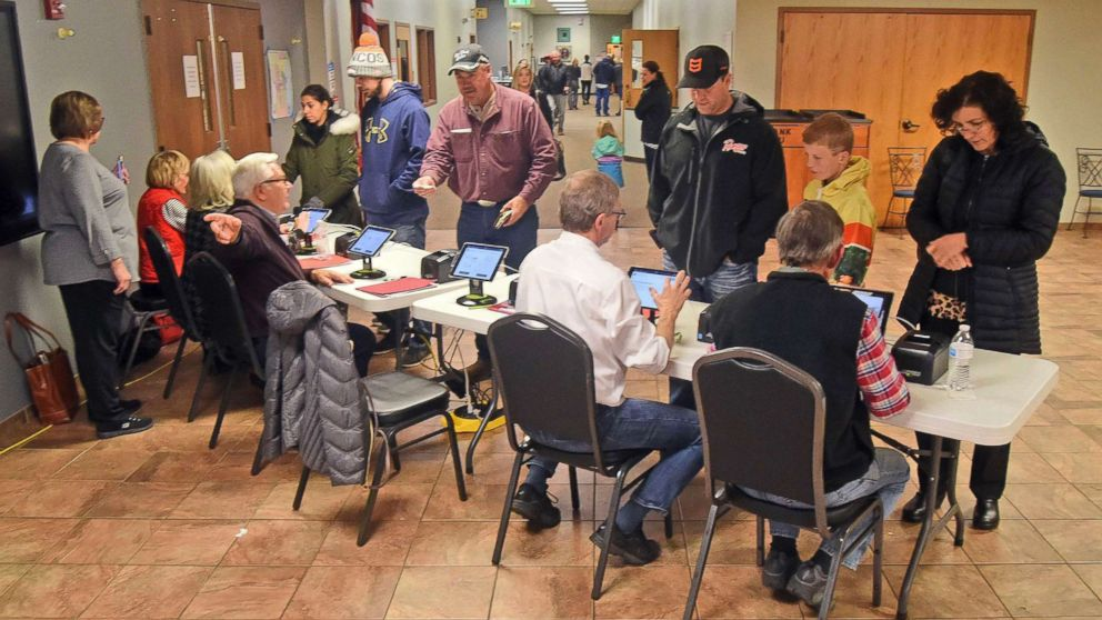 Election workers check identification of each person before receiving a ballot at the northwest Bismarck, N.D., polling place in Century Baptist Church on Tuesday, Nov. 6, 2018.