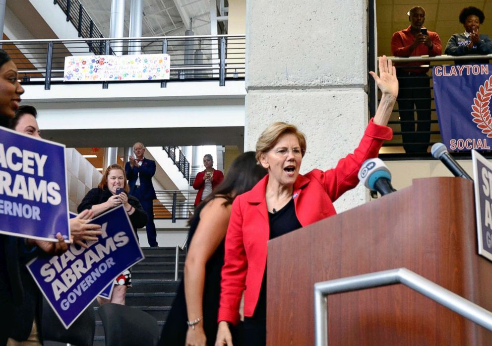PHOTO: Elizabeth Warren, Senator from Massachusetts, raises her hand during a meeting of Georgian gubernatorial election campaign in the suburb of Atlanta, on Oct.9, 2018.