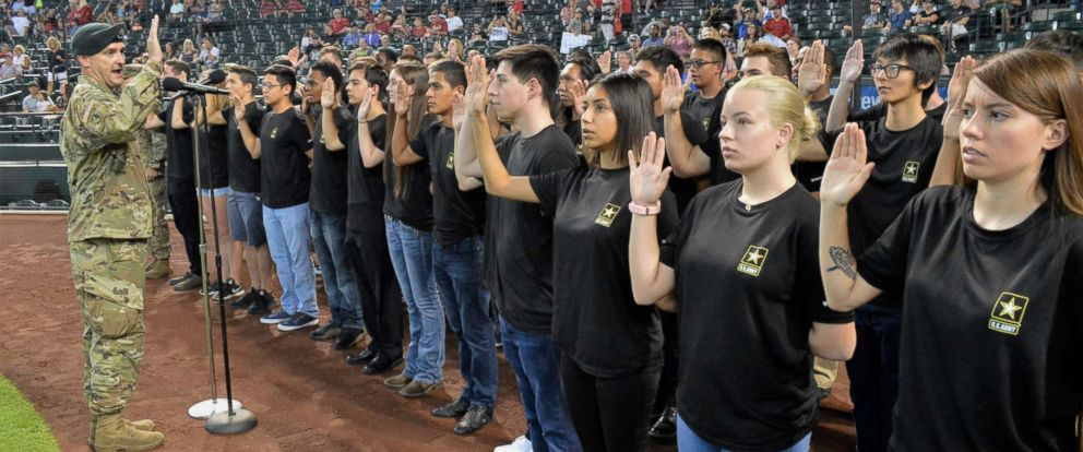 PHOTO: The Commander of the Phoenix Recruiting Battalion administers the oath of enlistment to a group of future soldiers before a Major League Baseball game in Phoenix, Aug. 26, 2018.