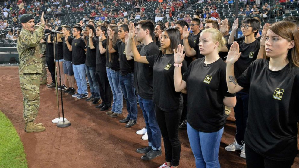 The Commander of the Phoenix Recruiting Battalion administers the oath of enlistment to a group of future soldiers before a Major League Baseball game in Phoenix, Aug. 26, 2018.