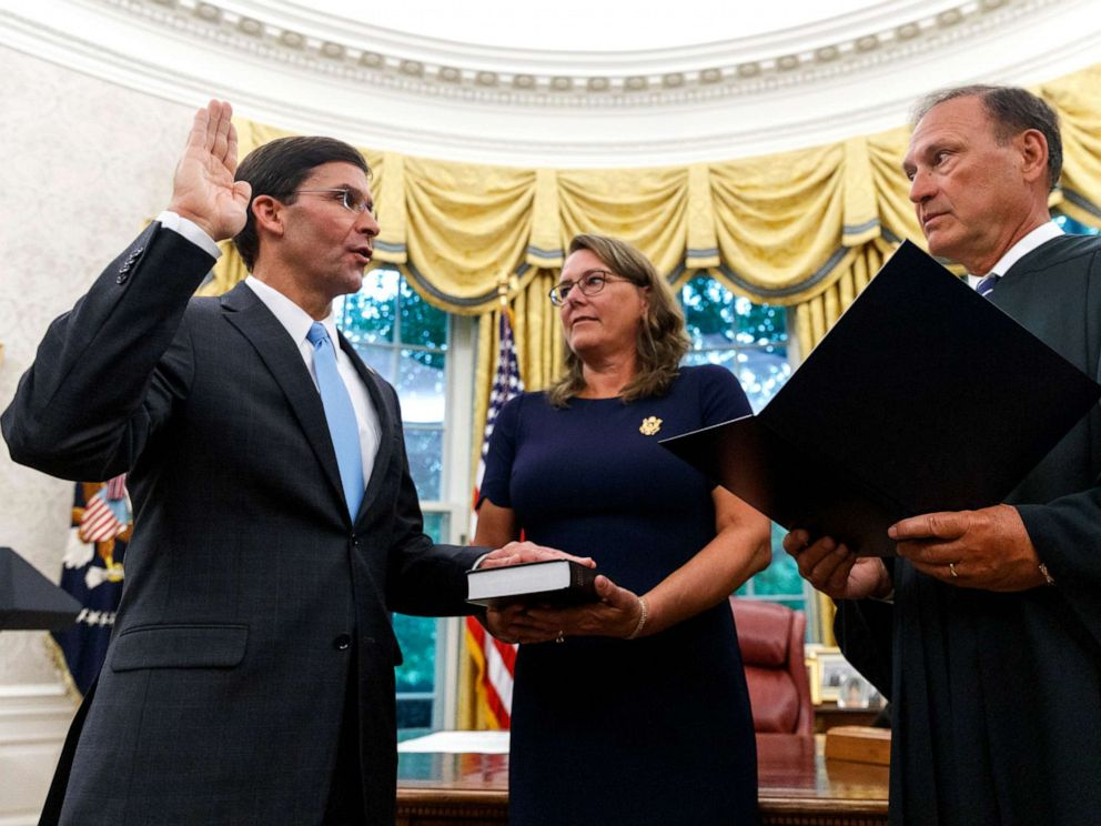 PHOTO: Mark Esper, left, is sworn in as the Secretary of Defense by Supreme Court Justice Samuel Alito, right, as is wife Leah Esper holds the Bible, during a ceremony in the Oval Office at the White House in Washington, July 23, 2019.