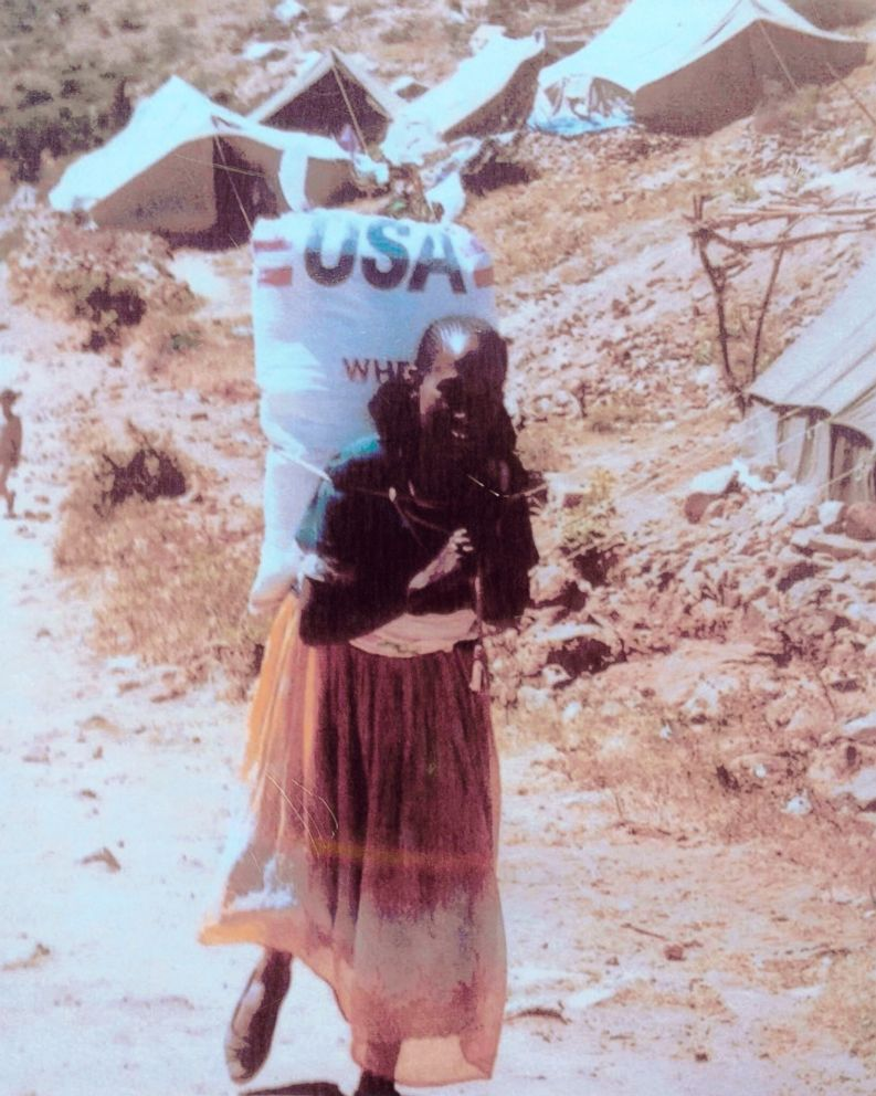 Photo taken by Patti Garamendi of a woman carrying 110-pound bag of grain.