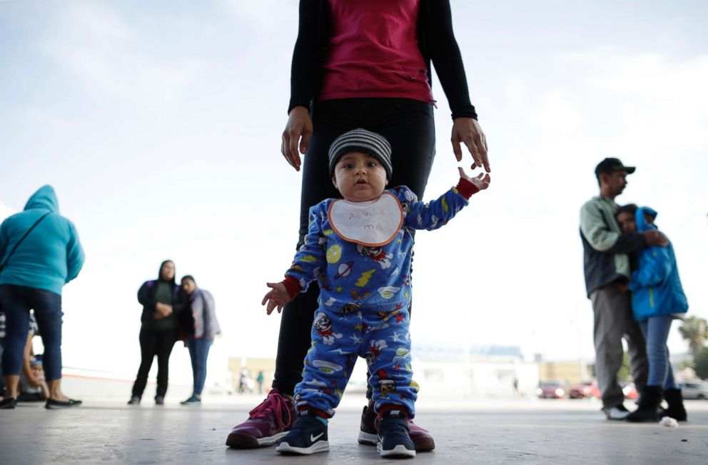 In this June 13, 2018 photo, nine month-old Jesus Alberto Lopez, center, stands with his mother, Perla Murillo, as they wait with other families to request political asylum in the United States, across the border in Tijuana, Mexico.