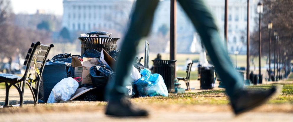 PHOTO: People walk past garbage on the National Mall on the fifth day of a partial federal shutdown in Washington, Dec. 26, 2018.