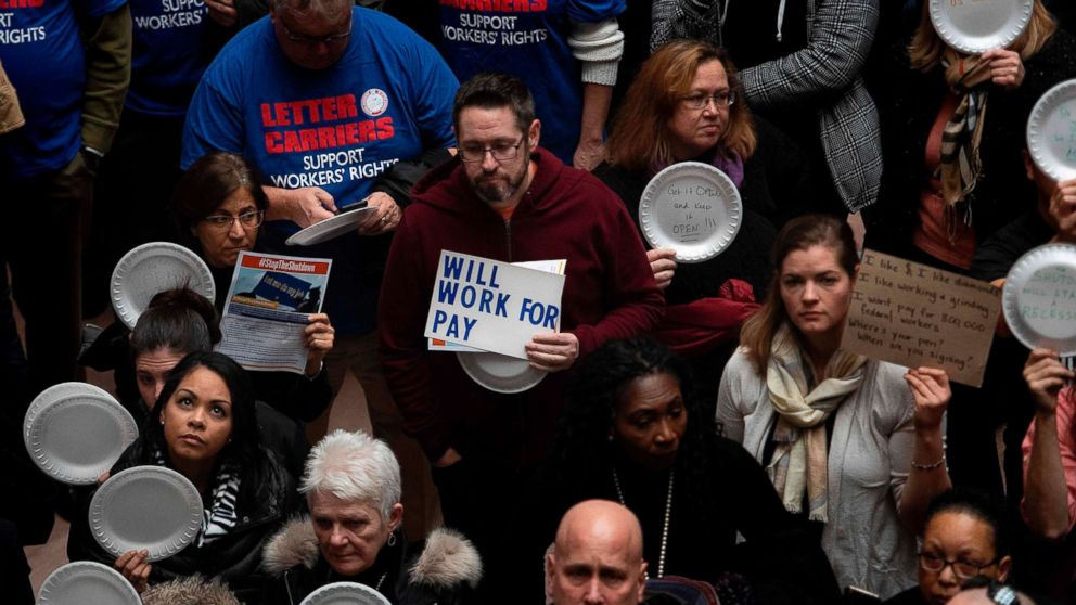 """A federal worker stands with a placard reading """"Will Work For Pay"""" as other federal employees stage a rally to call for a vote on the shutdown on Capitol Hill in Washington, Jan. 23, 2019."""