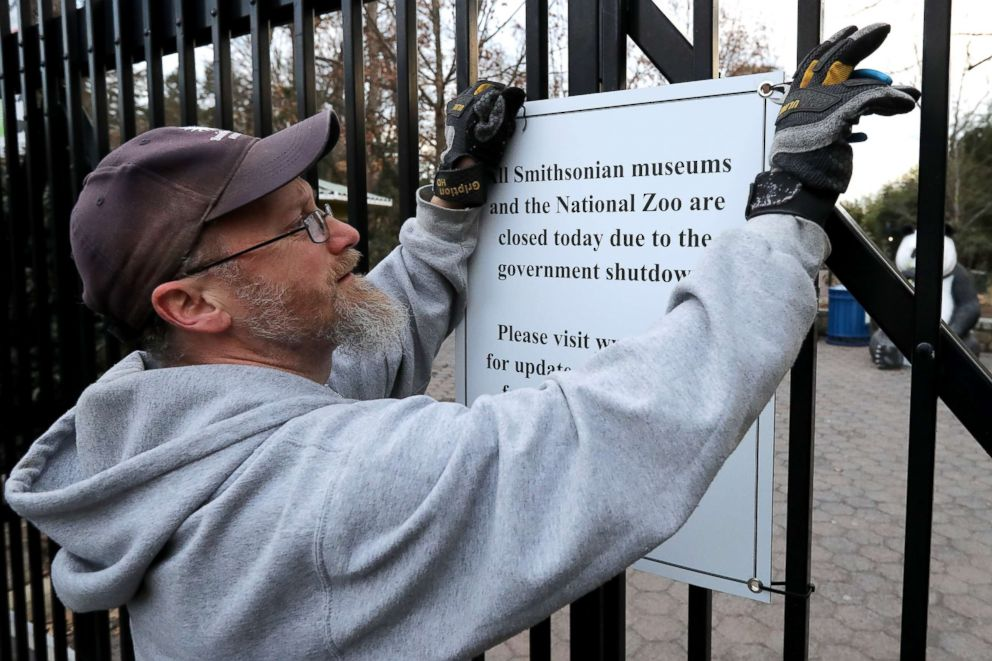 PHOTO: A Smithsonian National Zoo employee removes a sign telling visitors that the zoo is closed due to a government shutdown from the front gate, Jan. 28, 2019, in Washington, D.C.
