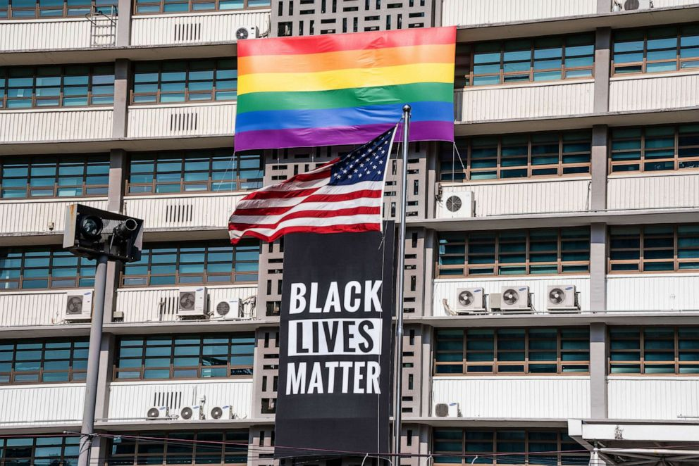 PHOTO: A Black Lives Matter banner, a United States national flag and a rainbow flag are hung on the facade of the US embassy building in Seoul, June 14, 2020.
