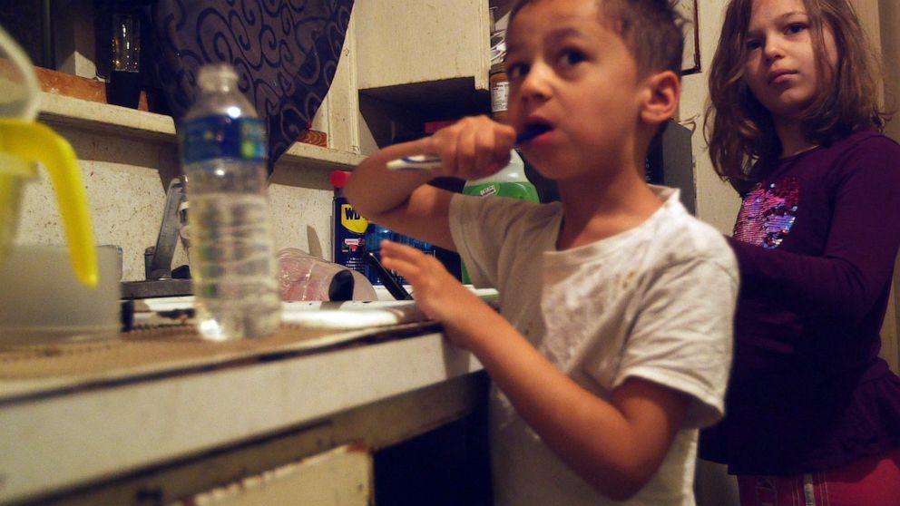 PHOTO: Gabriel and Nala Uherek brush their teeth using bottled water in their familys home in Flint, Mich.