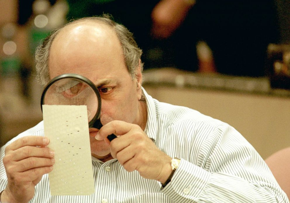Judge Robert Rosenberg of the Broward County Canvassing Board uses a magnifying glass to examine a dimpled chad on a punch card ballot, Nov. 24, 2000, during a vote recount in Fort Lauderdale, Florida.