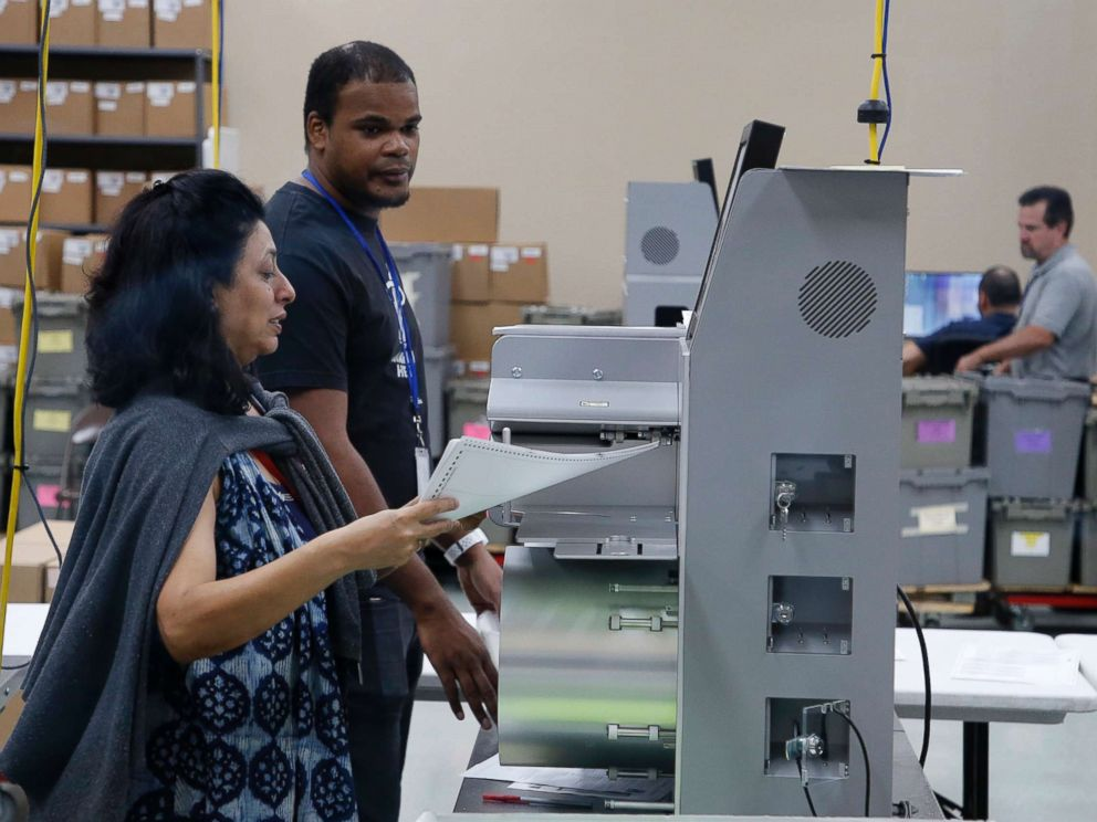 PHOTO: An elections employee feeds ballots into a tabulation machine at the Broward County Supervisor of Elections express of job on Nov. 10, 2018 in Lauderhill, Fla.