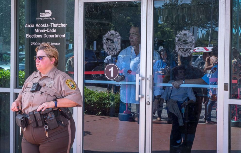 PHOTO: A police officer guards the entrance of the Miami-Dade Election Department while a crowd protests to demand the vote recount outside this facility in Miami, Nov. 10, 2018.