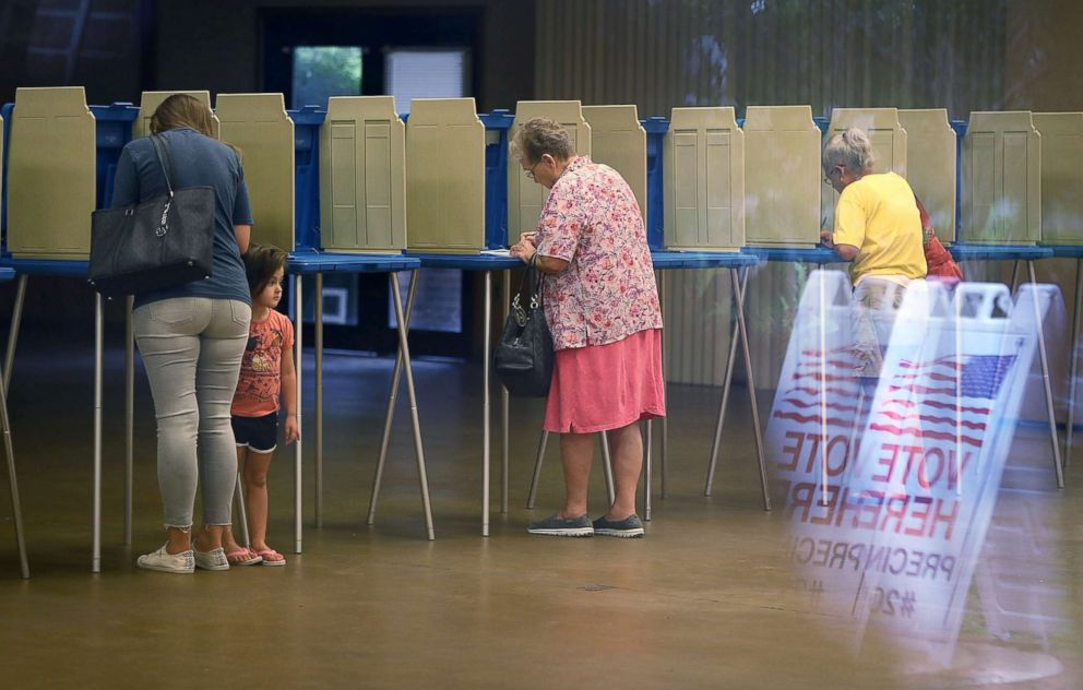 PHOTO: Fionna Beazzo stands with her mother Erin Beazzo as she fills out her primary day voting ballot next to Beverly Putzke at a polling station, Aug. 28, 2018, in St. Augustine, Fla.