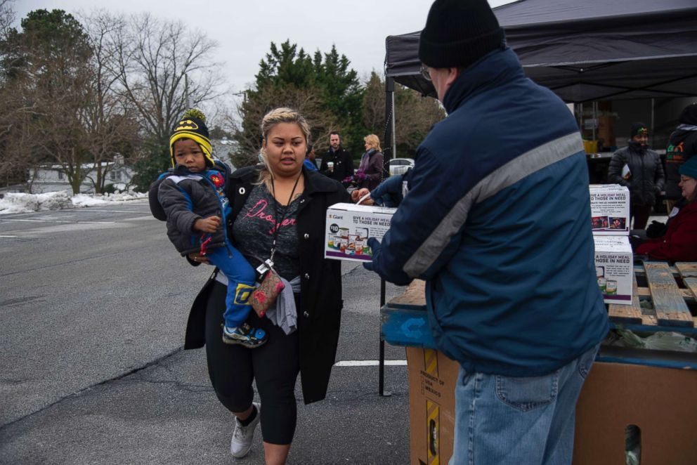 A State Department employee carries her son to collect food from a food bank passing out canned goods and produce to federal workers outside a Giant grocery store in Alexandra, Va., Jan. 19, 2019.