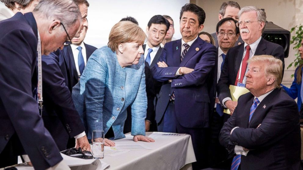In this photo made available by the German Federal Government, German Chancellor Angela Merkel, center, speaks with U.S. President Donald Trump, seated at right, during the G7 Leaders Summit in La Malbaie, Quebec, Canada, June 9, 2018.