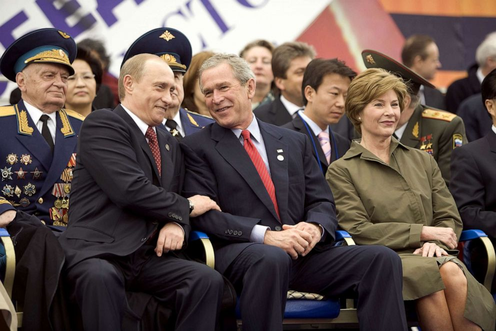 W. Bush center and Russian President Vladimir Putin left share a light moment as they sit with Laura Bush right and other heads of state during a military parade in Red Square in Moscow