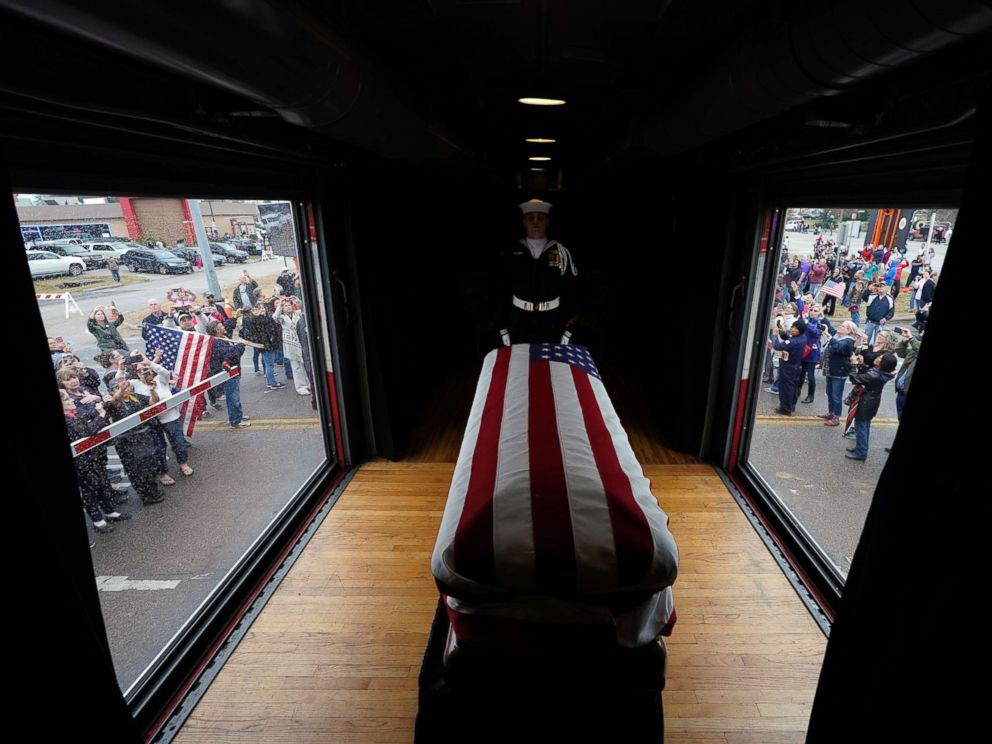 PHOTO: The flag-draped casket of former President George H.W. Bush passes through Magnolia, Texas, Dec. 6, 2018, along the train route from Spring to College Station, Texas.