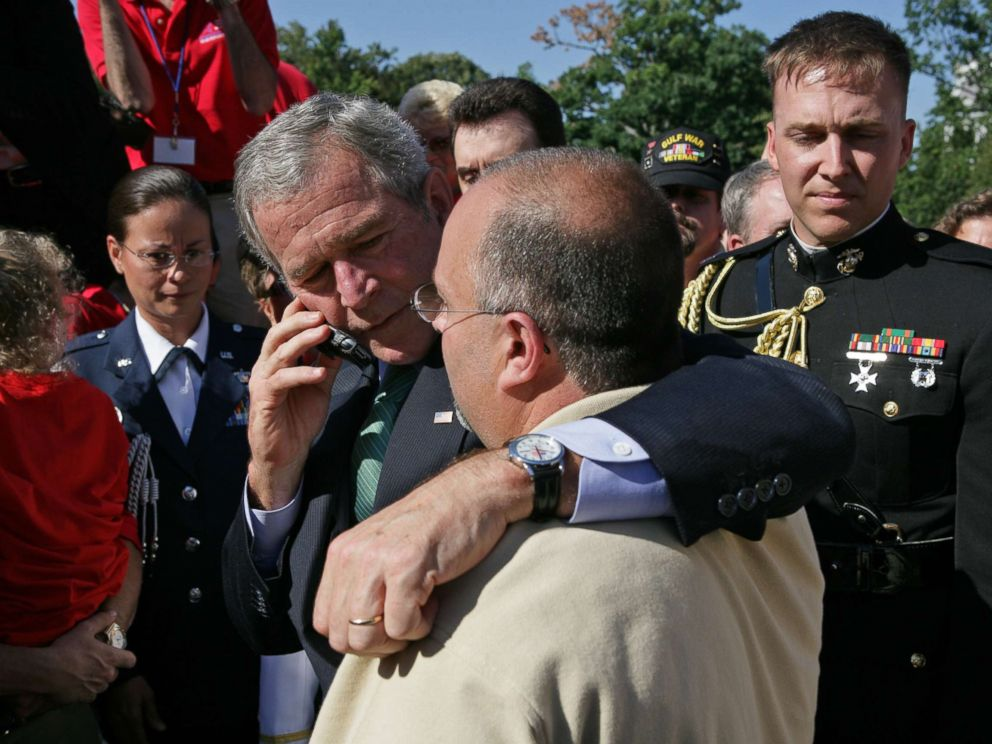 PHOTO: President George W. Bush stands with his arm around Jeff Hallal while speaking on the phone to his wife, Pam Hallal, Sept. 18, 2007 on the South Lawn of the White House.
