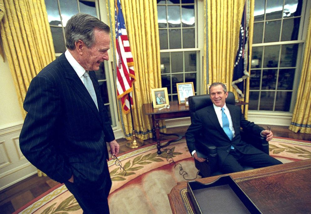 PHOTO: President George W. Bush sits at his desk in the Oval Office for the first time on Inaugural Day, in this Jan. 20, 2001 file photo, as his father, former President George H.W. Bush looks on.