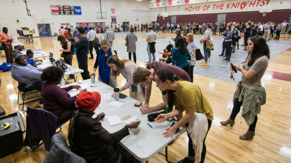 Voters line up to cast their ballots at a polling station set up at Grady High School for the mid-term elections, Nov. 6, 2018 in Atlanta.
