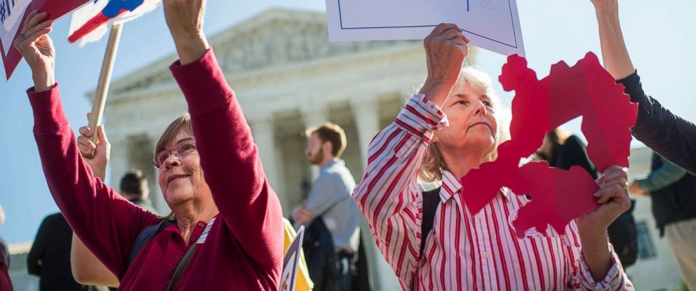 PHOTO: Holding up a sign representing a Texas district, Shirley Connuck, right, waits outsides the Supreme Court as a case on possible partisan gerrymandering by state legislatures is heard, Oct. 3, 2017.