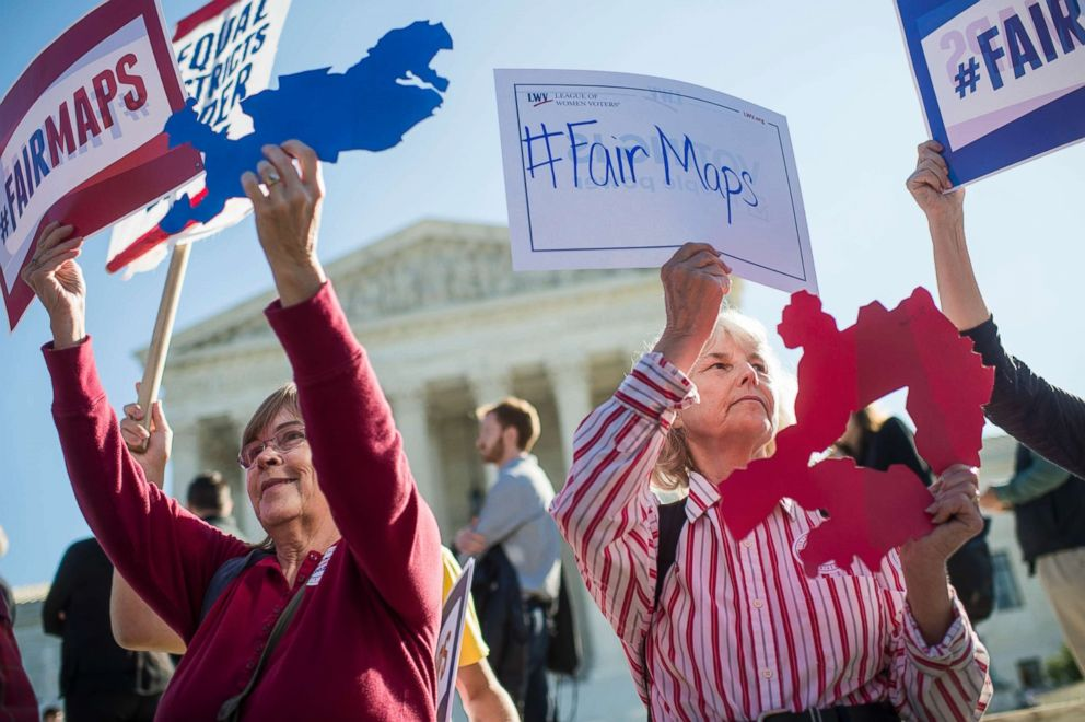 PHOTO: Shirley Connuck, right, of Falls Church, Va., holds up a sign representing a district in Texas, as the Supreme Court hears a case on possible partisan gerrymandering by state legislatures Oct. 3, 2017, in Washington, D.C.