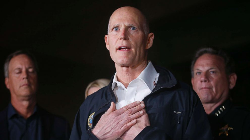 Florida Gov. Rick Scott gestures as he speaks during a news conference near Marjory Stoneman Douglas High School in Parkland, Fla., where a former student is killed at least 17 people on Feb. 14, 2018.