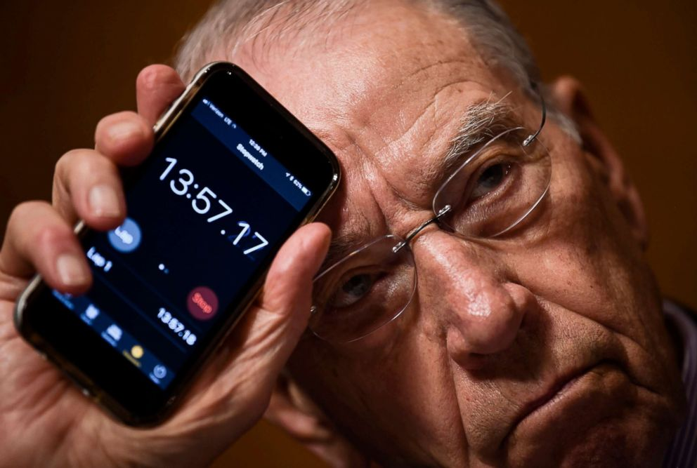 Senate Judiciary Committee Chairman Charles Grassley holds up his phone to show the time that Sen. Cory Booker has been speaking during a markup hearing on Capitol Hill in Washingto,n on Sept. 28, 2018, for the Supreme Court nomination of Brett Kavanaugh.