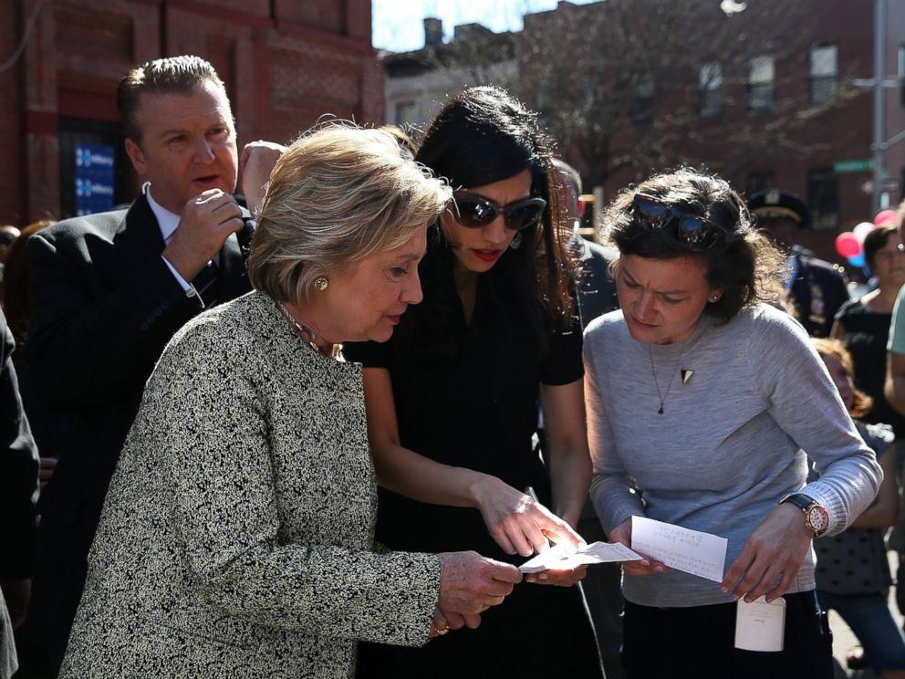 PHOTO: Hillary Clinton (L) talks with aides Huma Abedin (C) and Connolly Keigher before speaking at a neighborhood block party, April 17, 2016, in Brooklyn, New York.
