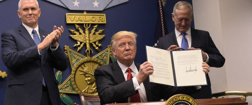PHOTO: President Donald Trump shows his signature on an executive order alongside Defense Secretary James Mattis and Vice President Mike Pence on Jan. 27, 2016 at the Pentagon in Washington, DC.